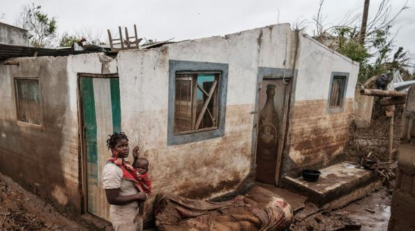 A woman holds her son in front of their destroyed home in Buzi, Mozambique