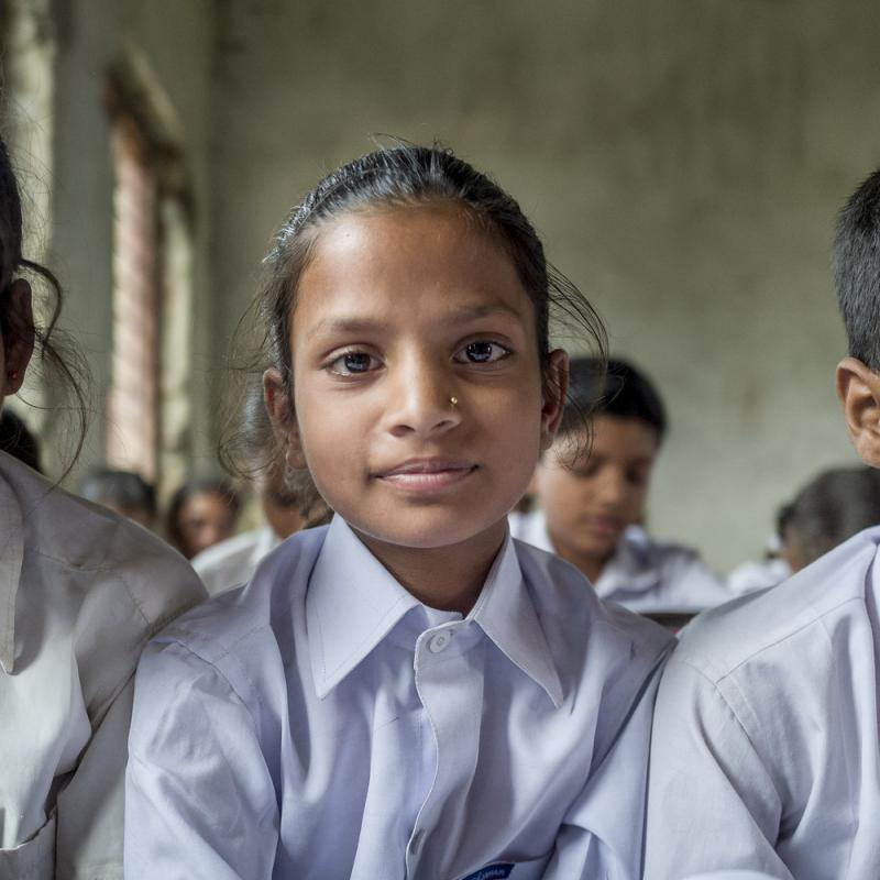 Two young girls and young boy sit and read from their textbooks in a busy classroom