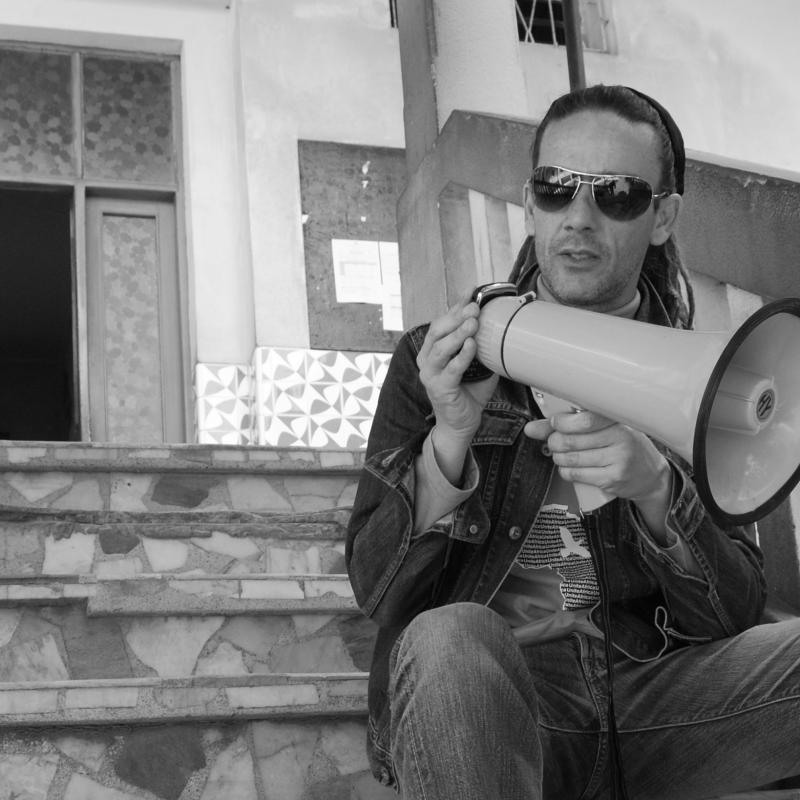 Darren Clark pictured here sat on steps with a megaphone.