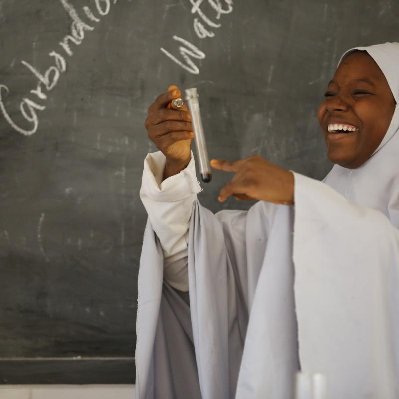 Girl with test tube in Nigerian classroom