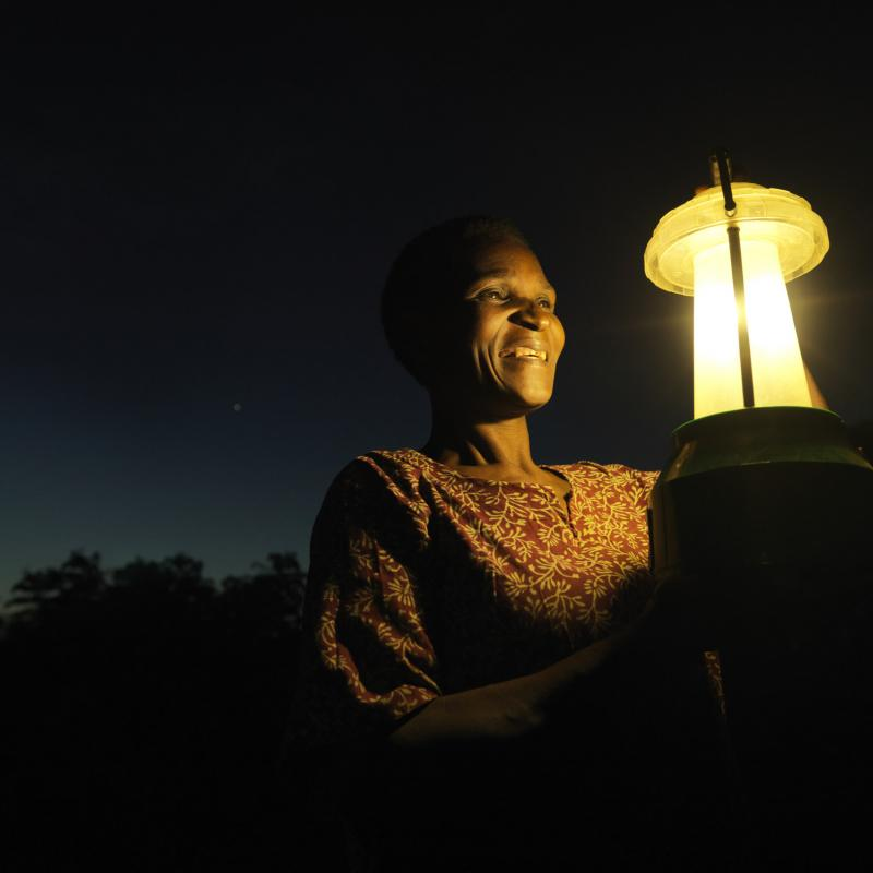 Woman with solar lantern at night in Malawi Africa | VSO