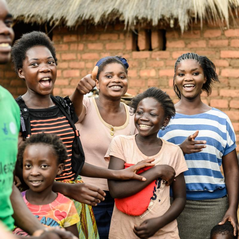 group of people in zambia smiling and laughing at the camera