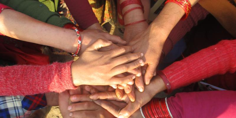 Women in Nepal holding hands during an intervention session