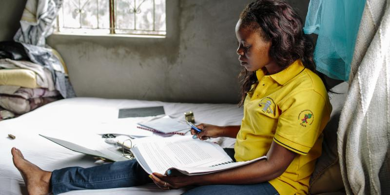 A female student studies whilst sitting on her bed