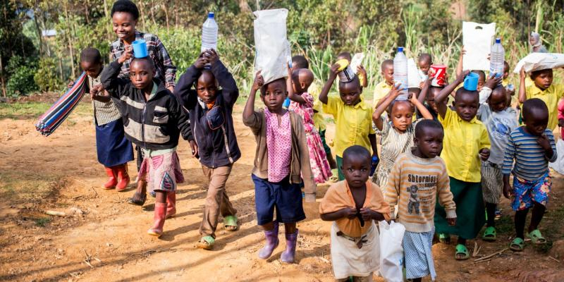 A group of young children carry teaching materials as they walk outside, led by their teacher
