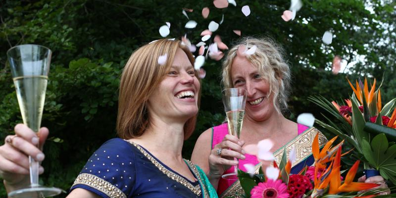 Jo and Beth, with confetti falling, holding champagne glasses, at their wedding last year