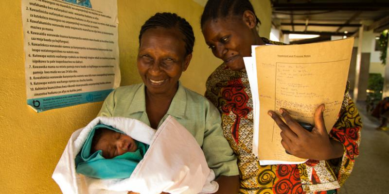 Nurse holding files with a mother and her newborn baby in Tanzania