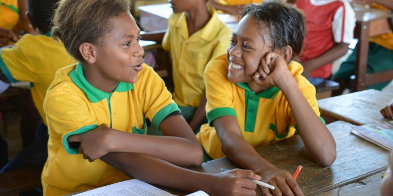 Two girls at Kusbau primary school in Madang discussing a text in a language lesson