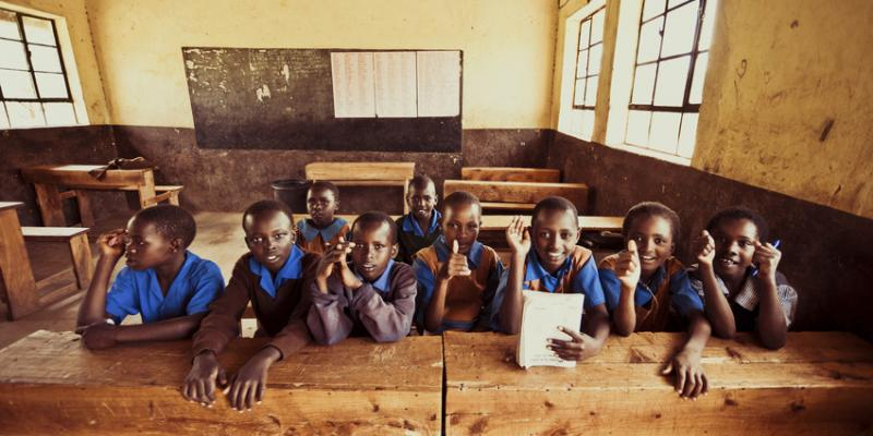 Children sitting at a bench at a school in Kenya