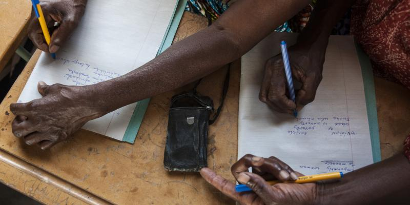 Students take notes during an Economic Empowerment training taught by women who have been trained by Voluntary Service Overseas (VSO) in conjunction with Caritas in Chembe, Zambia