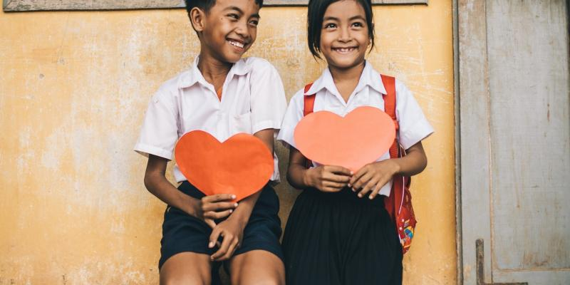 Children hold paper hearts in Cambodia