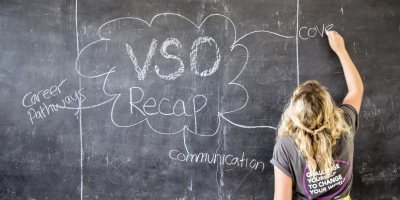 a VSO volunteer uses the blackboard in a classroom