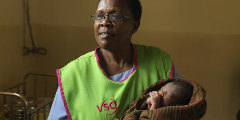 A VSO volunteer holding a newborn baby
