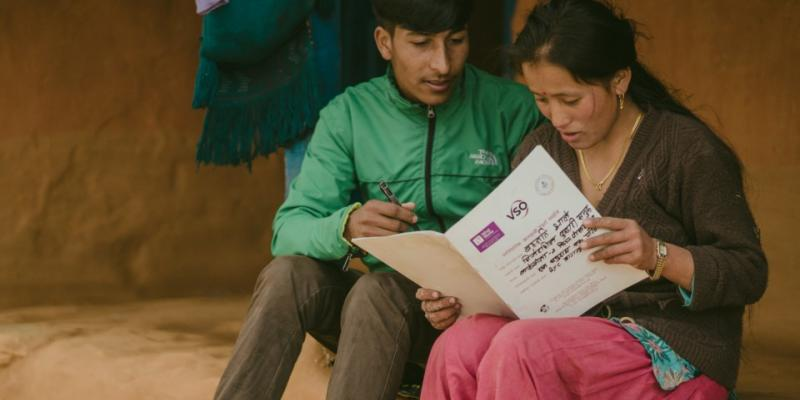 People read a VSO document as part of the One Community, One Family research project in Nepal