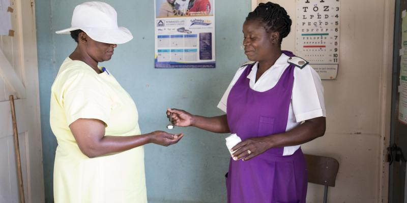 Sally*, an HIV+ peer educator at Chikurubi Female Prison, receives her anti-retroviral medication from nurse Rosina Brekwa in the prison clinic.