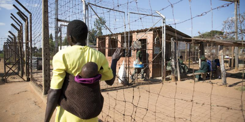 An inmate stands at the fence of Chikurubi Female Prison, Zimbabwe.