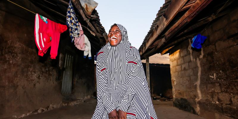 Fatima Al Hassan from Niger, Nigeria, is a farmer on the IMA4P project. Here she is smiling and laughing by her house.