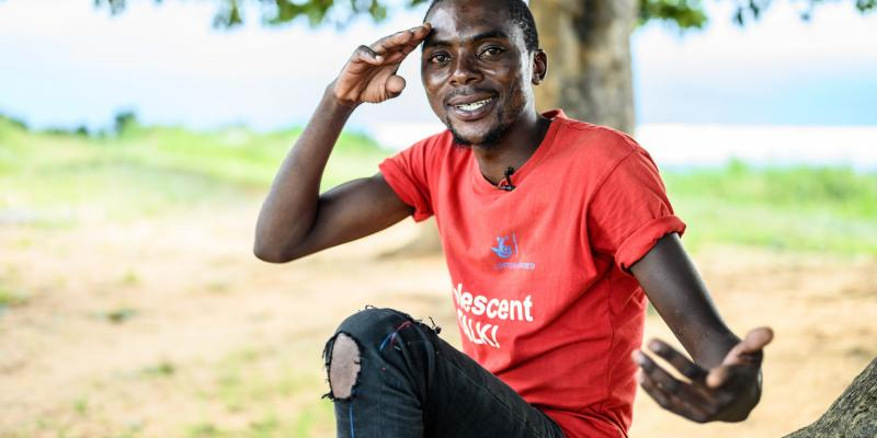 Alfred Mwiza holds his hands up while posing for a photo by the shores of the lake