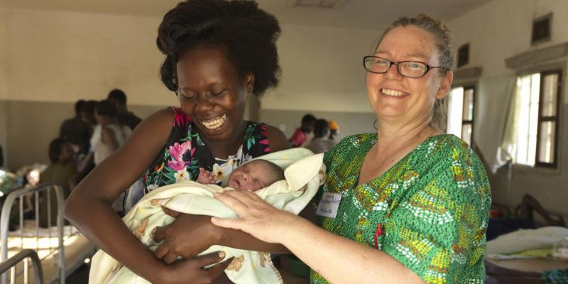 Leticia Dai, 23, with her first born and her VSO midwife Gudrun Witt.