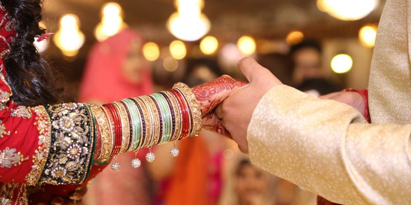 Pakistani couple at wedding, close-up of them holding hands