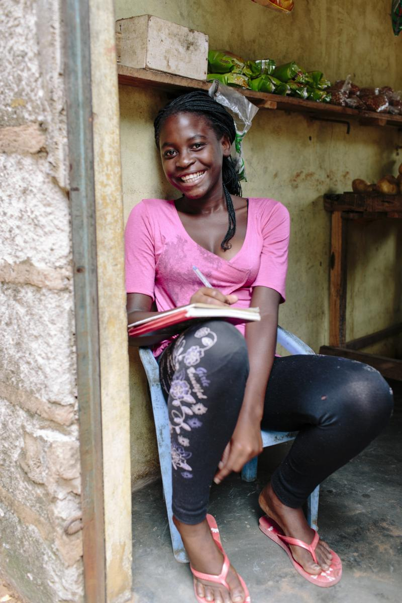 15-year-old Linda smiles as she sits in the doorway of her home, with her schoolwork resting on her knee