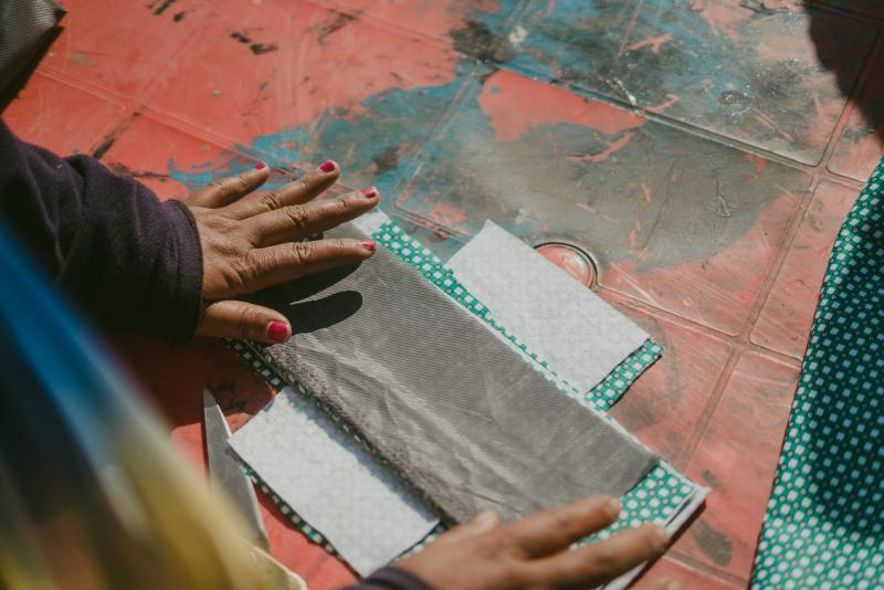 A big sister in Nepal demonstrates how to make reusable sanitary pads.