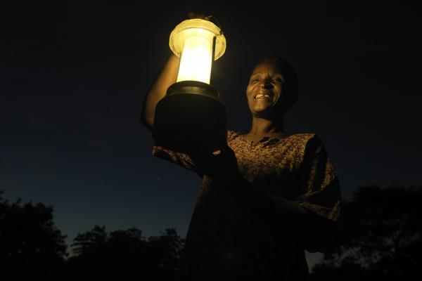 A woman's smiling face is illuminated by the solar lantern she holds up as she stands outside at nighttime