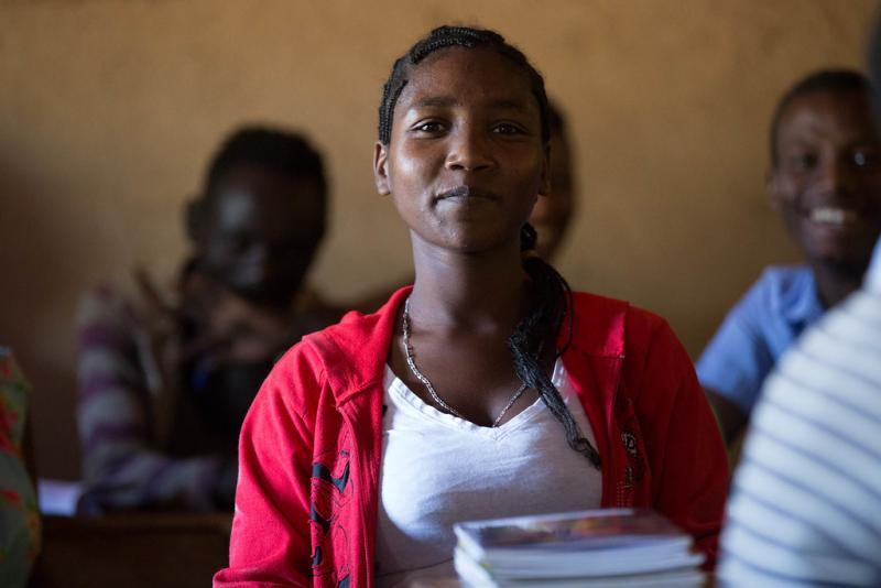 Zena Boko, Age 16, Grade 8, smiles sitting in class having returned to school.