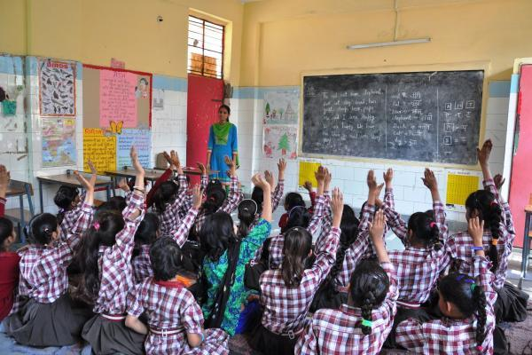 Girls sit on the floor of their classroom and raise their hands; at the front, a young female teacher stands by the blackboard