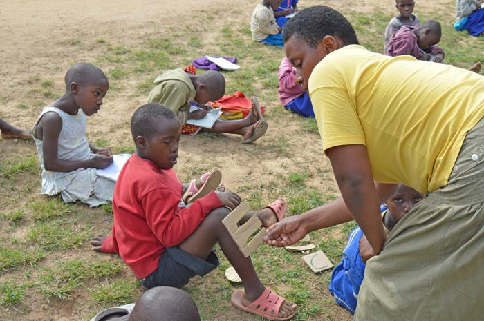 Teacher in class with boy with intellectual disabilities in Rwanda | VSO