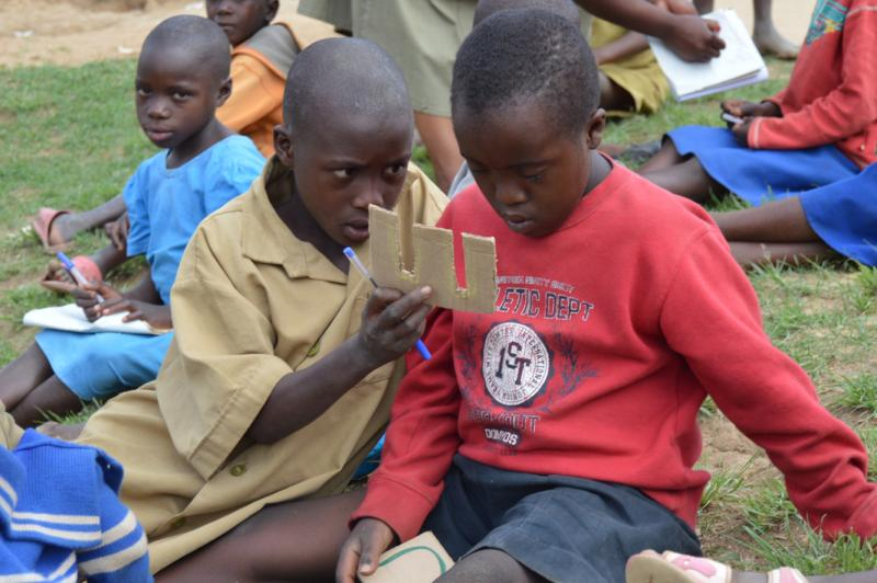 Two boys using disability friendly teaching and learning materials in a class in Rwanda | VSO