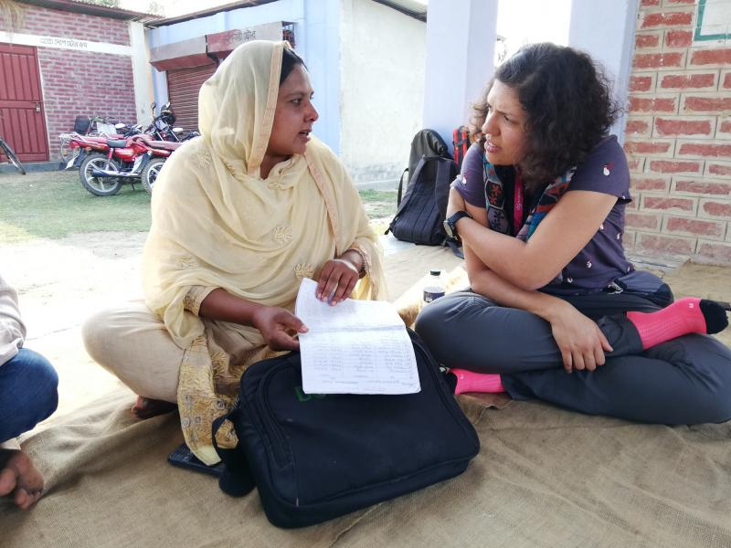 Two women sat on the floor outside, in conversation and holding papers