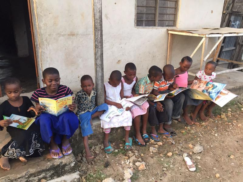 Children reading on a step in Tanzania