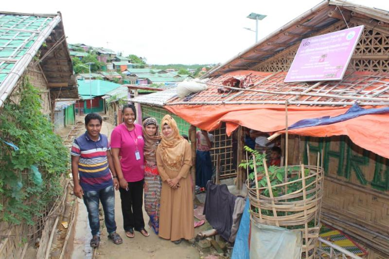 Ann Wambui stands with community volunteers and a Rohingya mother, in Cox's Bazar refugee camp