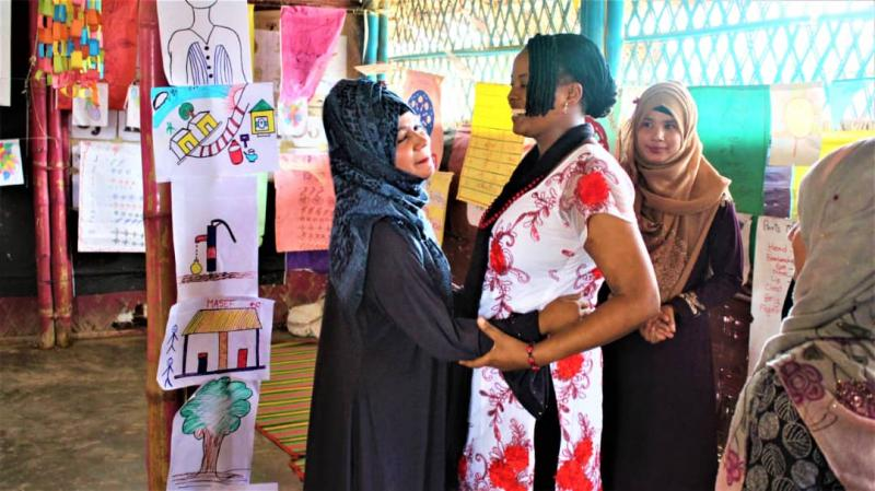 VSO volunteer Ann Wambui with rohingya mother Shofika, smiling and happy.