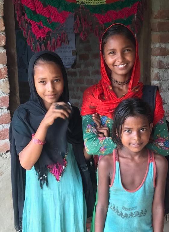 Three smiling Nepali girls who are attending VSO-led 'bridge-classes'.