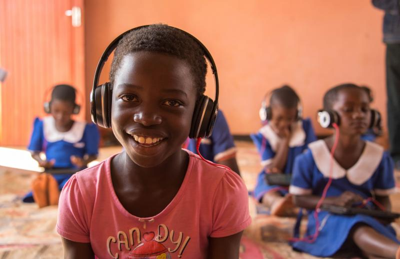 A young pupil smiles whilst wearing headphones as part of an Unlocking Talent lesson