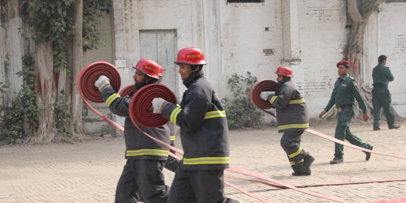 Volunteer firefighters perform an exercise with VSO Pakistan partner Rescue 1122