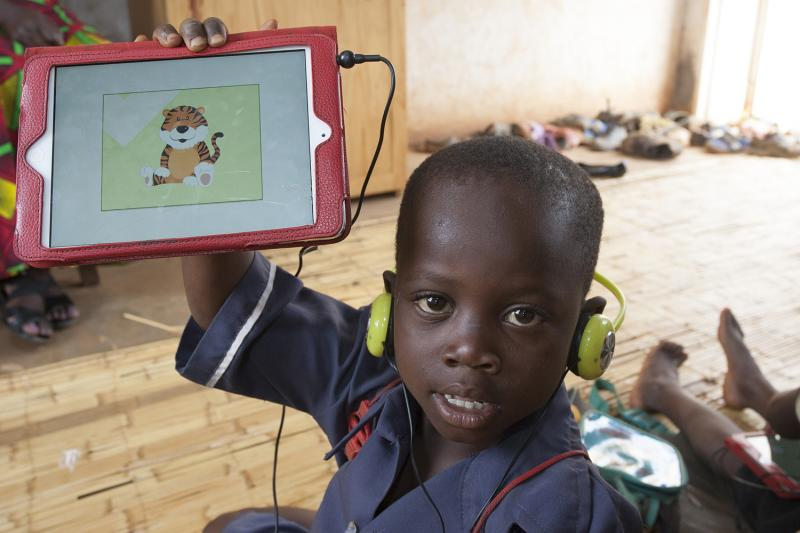 Alex Kachigamba shows off his certificate on his tablet after he successfully completed a lesson during the Unlocking Talent Through Technology class session at Biwi Primary School in Lilongwe
