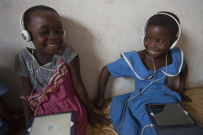 Two girls enjoy using the Unlocking Talent software in Malawi