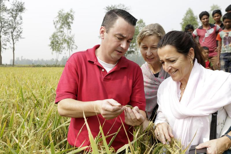 Greg Gungoll shows a warm to Marie and Antonia in a paddy filed at Sagayhata, Birampur, Bangladesh