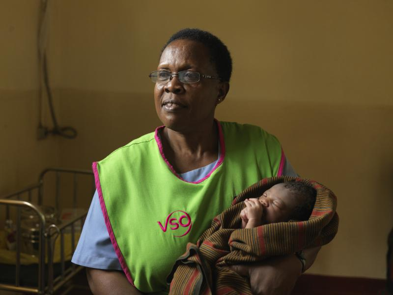 A VSO midwife holding a baby