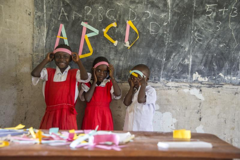 Children stand by the blackboard in a Kenyan classroom