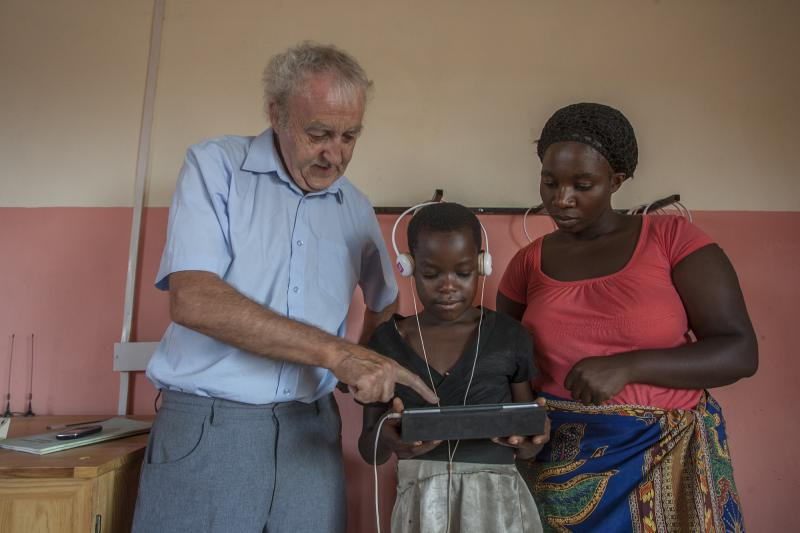 Volunteer Sean demonstrates tablet computer with teacher in Malawi