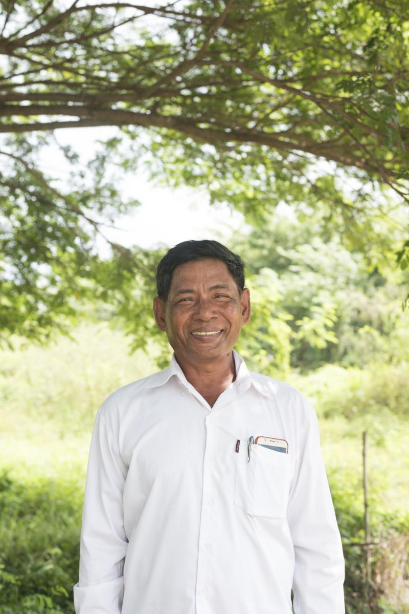 Prak Sim, a Cambodian farmer, smiling in a field. He has been taught better farming techniques to improve yields and incomes.