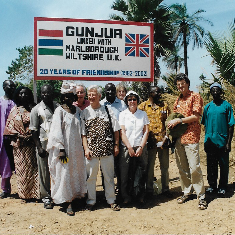 With local people in Gunjur, The Gambia in front of the sign declaring Gunjur linked to Marlborough (2002).