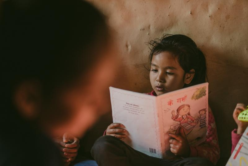 A child reads a book in a community library in Nepal