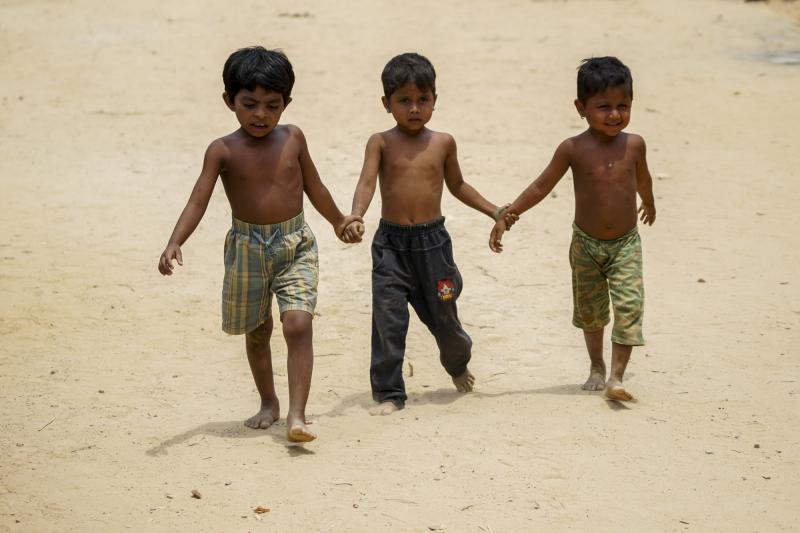 Three Rohingya children walk in the hillock of the Balukhali extension camp, Cox's Bazar, Bangladesh.