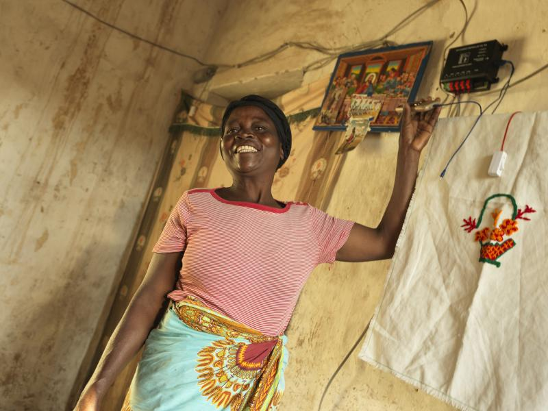 Woman with mobile phone charging business in Malawi | VSO2