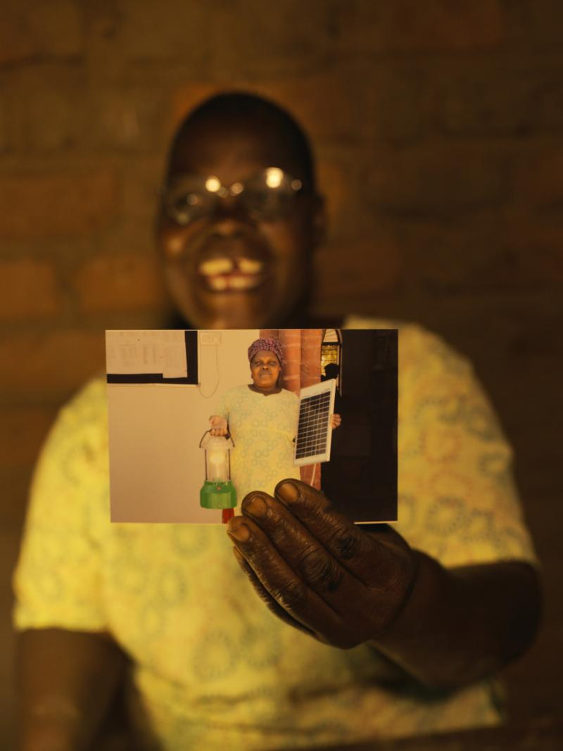 Malawian woman holds up a photograph